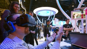 An attendee wearing an Oculus Rift virtual reality headset plays in a virtual volleyball game at the Intel booth during the 2015 International Consumer Electronics Show (CES) in Las Vegas, Nevada January 6, 2015. The goggles give a full 3D immersion and 360 degree view, a representative said. REUTERS/Steve Marcus (UNITED STATES - Tags: SCIENCE TECHNOLOGY BUSINESS) - RTR4KAO3